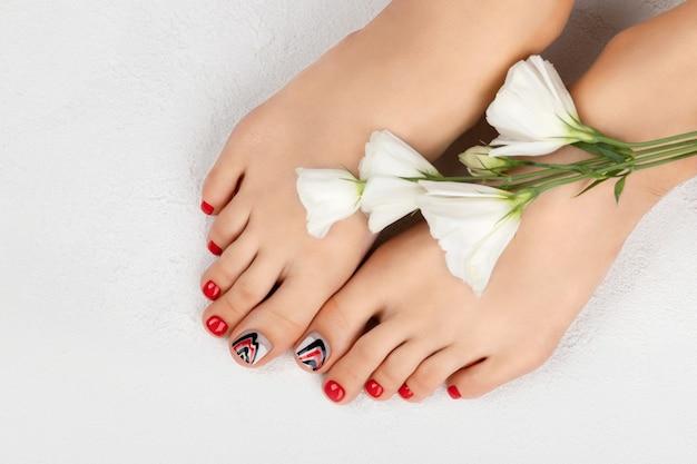 Concept de salon de beauté manucure pédicure pieds de femme sur gris