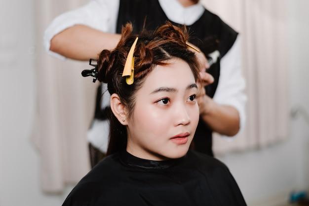 Concept de salon de coiffure un coiffeur masculin utilisant un peigne pour saisir une mèche de cheveux et utilisant un sèche-cheveux pour le séchage et le lissage