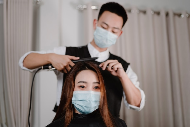 Concept de salon de coiffure à la fois coiffeur masculin et cliente portant un masque protecteur pendant le processus de coupe de cheveux.