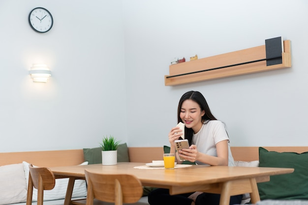 Concept de salon une femme adulte appréciant de manger des sandwichs et du jus d'orange en regardant les médias en ligne pendant la pause de travail.