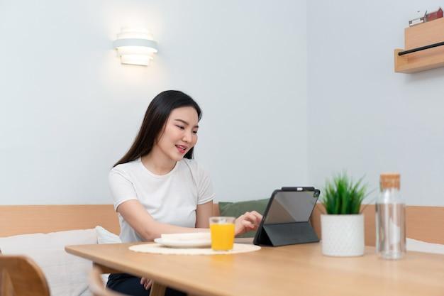Concept de salon une fille aux cheveux longs assise dans le salon surfant sur internet avec son smartphone.