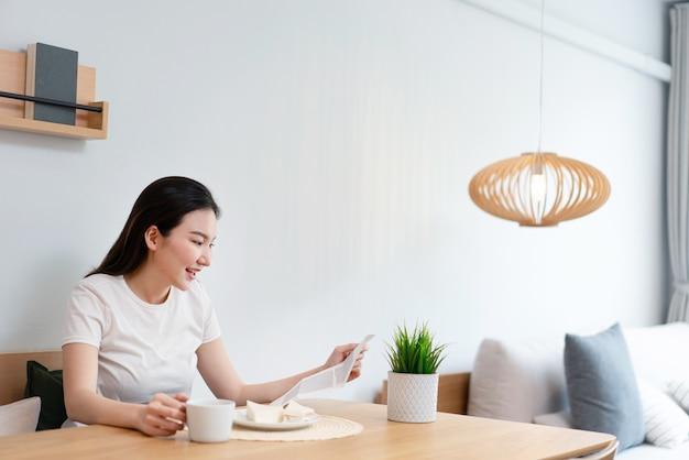 Concept de salon une jolie dame lisant l'article sur le papier tandis qu'une autre main tient une tasse de boisson à la caféine le matin.