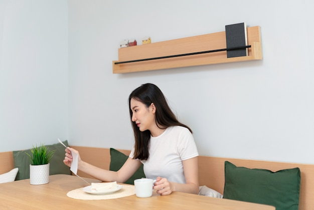 Concept de salon une jolie dame tenant un papier à lire tandis qu'une autre main tenant une tasse de caféine dans le salon.