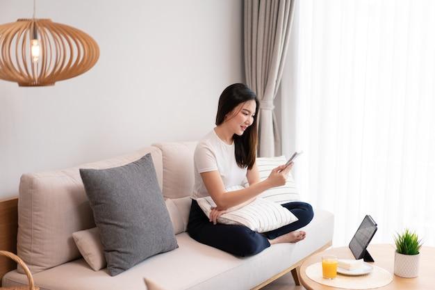 Concept de salon une jolie fille assise sur le canapé confortable passant ses loisirs en ligne avec du jus et des collations dans le salon.