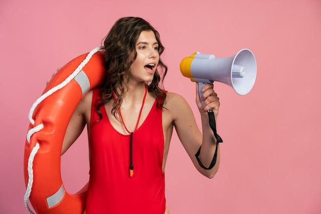 Concept de salut, avertissement de danger. une jeune fille aux cheveux bouclés et ondulés tient une bouée de sauvetage et dit quelque chose dans un haut-parleur.