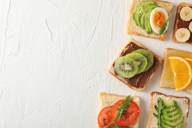 Concept avec des sandwichs assortis sur fond blanc, vue de dessus