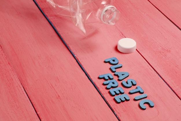 Concept sans plastique. bouteille froissée sur bois rouge