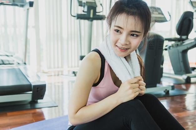 Concept de santé avec une femme en vêtements de sport se détendre et se détacher de l'exercice dans un centre de fitness