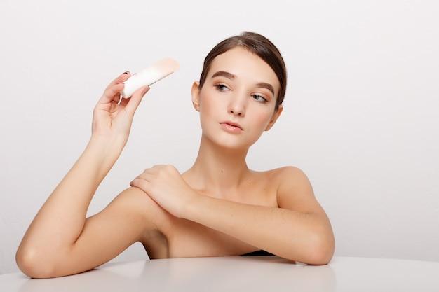 Concept de santé, de personnes et de beauté - visage de beauté d'une jeune femme avec une crème cosmétique sur une joue. concept de soins de la peau. closeup portrait isolé sur blanc. visage de jeune femme adulte avec une peau fraîche et propre.