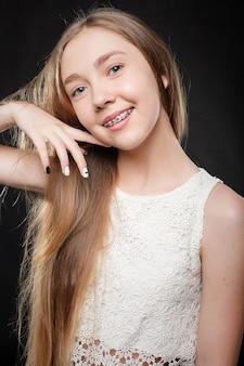 Concept de santé, de personnes, de jeunesse, de soins dentaires et de beauté - portrait d'adolescente montrant des appareils dentaires.