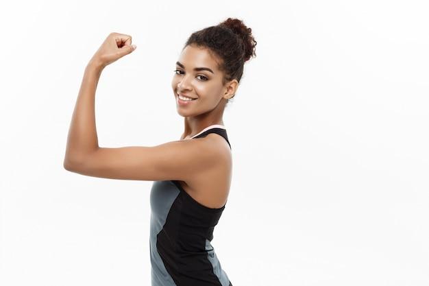 Concept de santé et de remise en forme - portrait de jeune belle afro-américaine montrant son dos musculaire avec une expression faciale gaie confiante. isolé sur fond de studio blanc.
