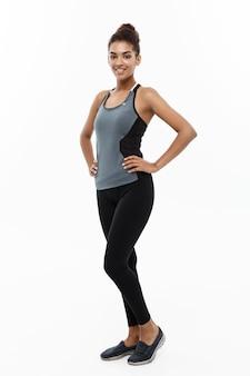 Concept de santé et de remise en forme - portrait de jeune fille afro-américaine posant avec des vêtements de fitness isolé sur blanc.