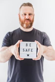 Concept de santé et de sécurité. homme tenant une boîte à lumière avec texte soyez en sécurité pendant les pandémies de coronavirus covid-19