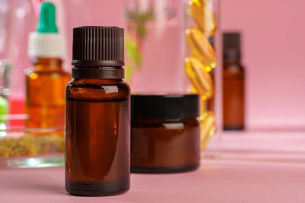 Concept de santé, de soins de la peau et de beauté. conteneurs cosmétiques sur fond rose avec des feuilles de plantes