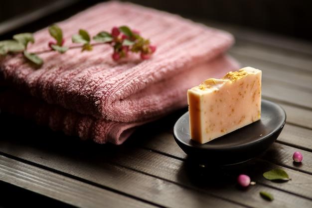 Concept de savon bio, cadeau fait main, barre de savon rose sur fond de bois, gros plan