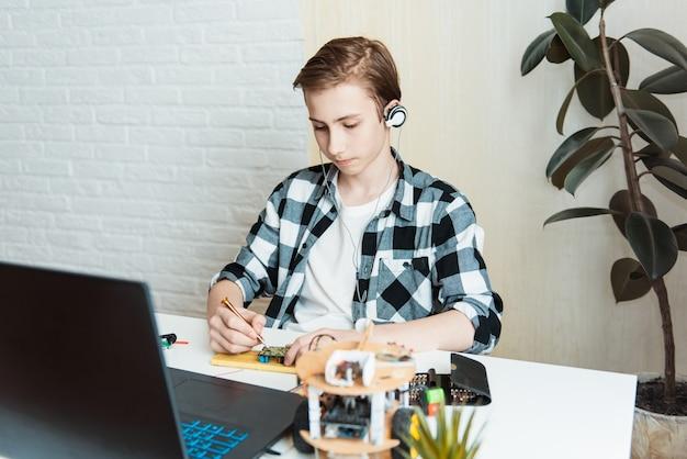 Concept de science, technologie, enfants et personnes de l'éducation - heureux adolescent garçon ou étudiant avec tablette pc programmation informatique jouets électriques à la leçon d'école de robotique