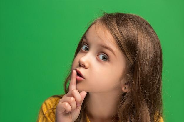 Concept secret, potins. jeune adolescente chuchotant un secret derrière sa main isolé sur fond de studio vert branché. jeune fille émotionnelle. émotions humaines, concept d'expression faciale.