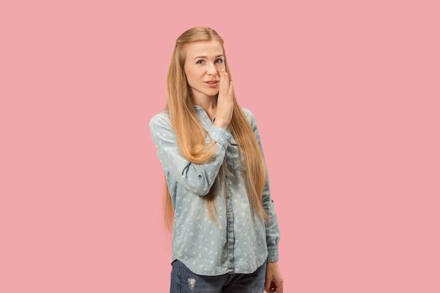 Concept secret, potins. jeune femme chuchotant un secret derrière sa main. femme d'affaires isolée sur fond de studio rose à la mode. jeune femme émotionnelle. émotions humaines, concept d'expression faciale.