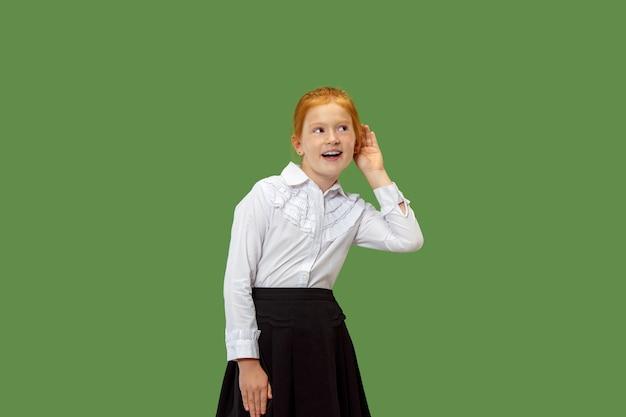Concept secret, potins. jeune fille chuchotant un secret derrière sa main. elle a isolé sur fond de studio vert à la mode. jeune adolescent émotionnel.