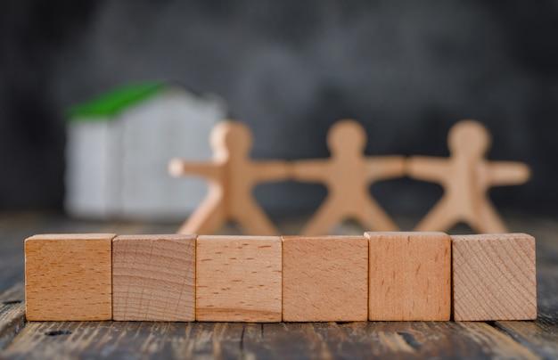 Concept de sécurité familiale avec des figures en bois de personnes, cubes, vue de côté de la maison modèle.