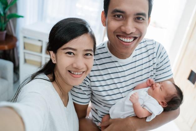 Concept de selfie, famille joyeuse portant petite fille