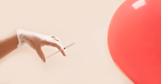 Concept avec seringue et main dans des gants injectant un ballon. spa, médecine, soins de santé, traitement, concept de beauté