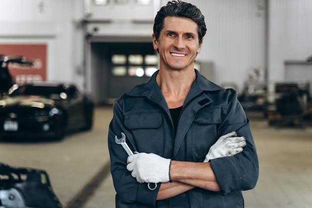 Concept de service, de réparation, d'entretien et de personnes de voiture. taille vue portrait de l'homme mécanicien automobile ou forgeron avec clé à l'atelier