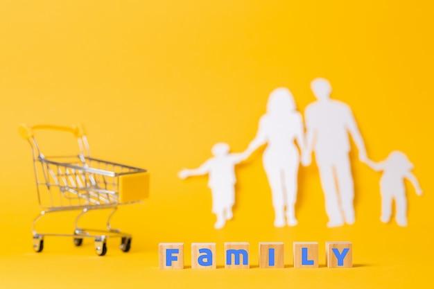 Le concept de shopping, de consommation et de rabais. un chariot vide et des blocs de bois avec la famille d'inscription.