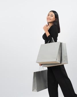 Concept de shopping femme. heureusement fille et sacs à provisions pendant la saison des soldes. heureuse jeune femme thaïlandaise asiatique en action ou activité d'achat de marchandises dans des magasins ou une boutique en ligne et fond blanc.