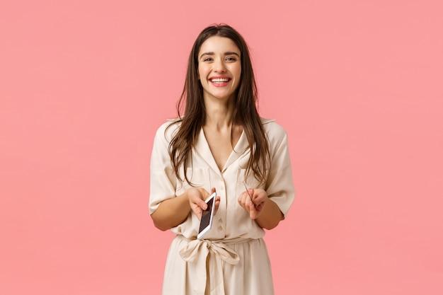 Concept de shopping, internet et beauté. joyeuse séduisante jeune femme en robe, tenant le téléphone et la carte de crédit, riant et souriant, commande en ligne, attente de livraison, insérer les informations de compte