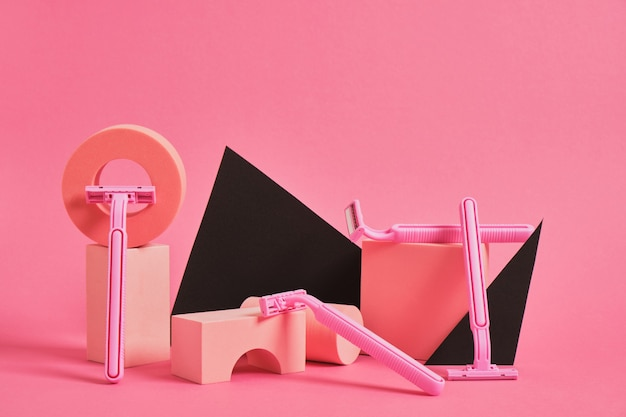 Concept de soins corporels pour femmes. divers stands et podiums géométriques et plusieurs rasoirs roses sur fond rose. art féministe