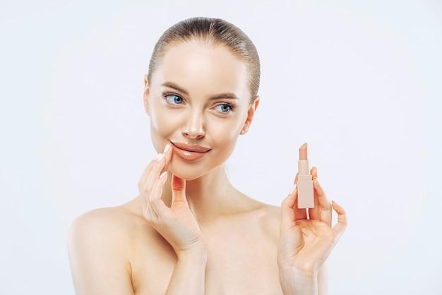 Concept de soins des lèvres. pensive belle femme aux cheveux noirs, pose avec un produit cosmétique, a un maquillage minimal, regarde sensuellement de côté, pose topless, a un corps bien soigné, isolé sur fond blanc