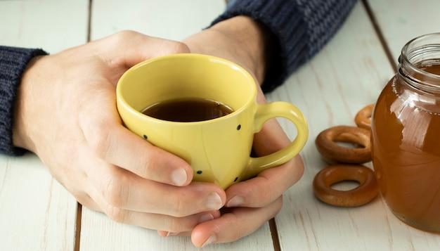 Concept de soins médicaux - mains tenant la tasse avec du miel au gingembre et du thé au citron avec des médicaments, des pilules.