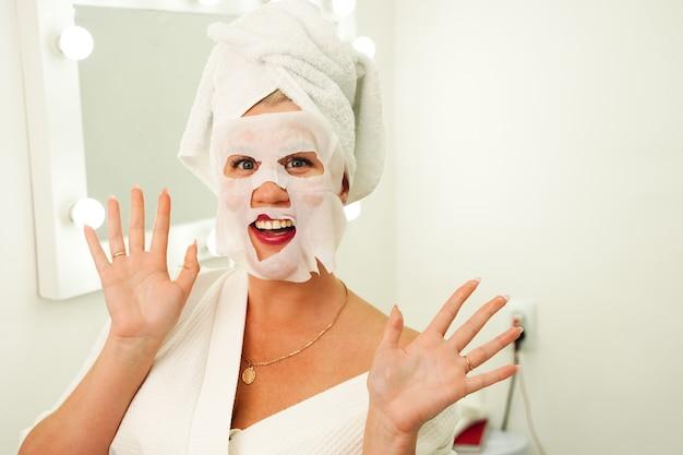 Concept de soins de la peau de beauté belle femme caucasienne appliquant un masque en feuille de papier sur son visage blanc
