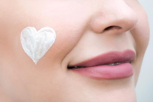 Concept de soins de la peau du visage. une jeune femme a un cœur de crème sur le visage.