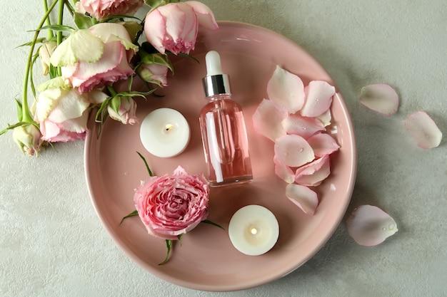 Concept de soins de la peau à l'huile essentielle de rose sur table texturée blanche
