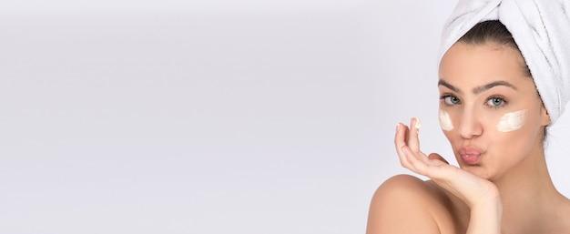 Concept de soins de la peau et de produits pour la peau, crèmes et hydratants. modèle de fille avec de la crème pour le visage sous les yeux et une serviette autour de sa tête.