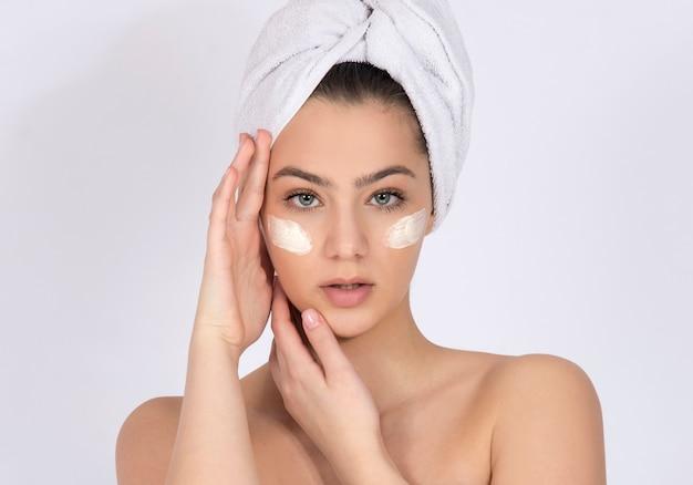 Concept de soins de la peau et de produits pour la peau, peau saine, crèmes et hydratants. modèle fille avec crème pour le visage sous les yeux et serviette sur la tête.