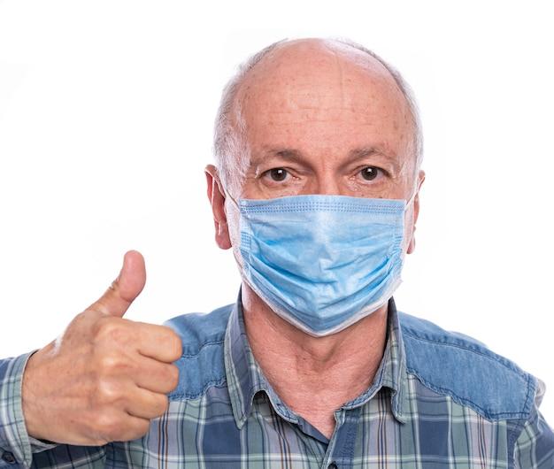 Concept de soins de santé. homme senior en masque de protection posant en studio sur fond blanc. gestes ok signe