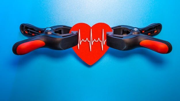 Concept de soins de santé et de médecine - gros plan d'un cœur rouge avec une ligne ecg serrée dans un étau pour la réanimation. salut de la vie et des sentiments. la saint-valentin.