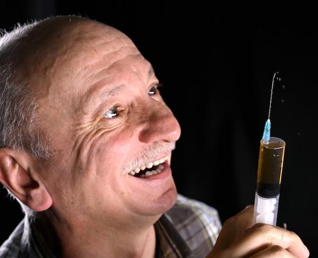 Concept de soins de santé et de médecine. senior man holding seringue sur fond noir