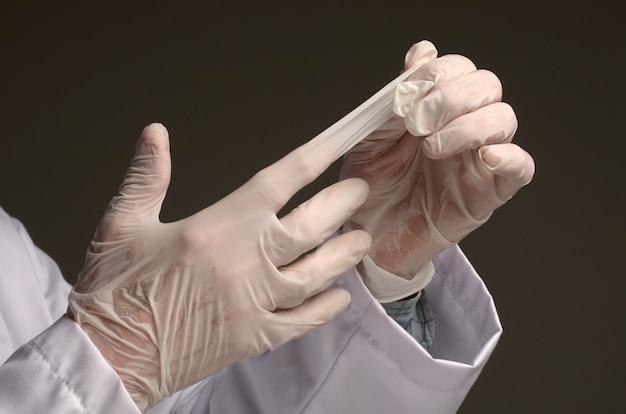 Concept de soins de santé et médical. l'homme qui décolle des gants chirurgicaux jetables en latex sur fond gris