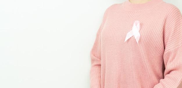Concept de soins de santé, de personnes, de médecine et de charité. femme en pull rose avec ruban de sensibilisation au cancer du sein sur blanc