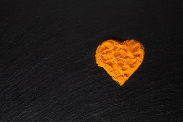 Concept de soins de santé poudre de curcuma d'épices en forme de coeur sur fond noir
