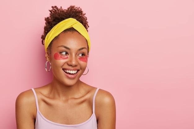 Concept de soins de santé et de procédures cosmétiques. heureuse fille ethnique aux cheveux bouclés, se dresse avec des patchs de maquillage sous les yeux, profite des soins de beauté, porte des vêtements décontractés