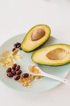 Concept de soins de santé et de régime alimentaire. avocat et huile de poisson en capsules pour la vitamine d et les acides gras oméga-3 dans une assiette sur fond blanc