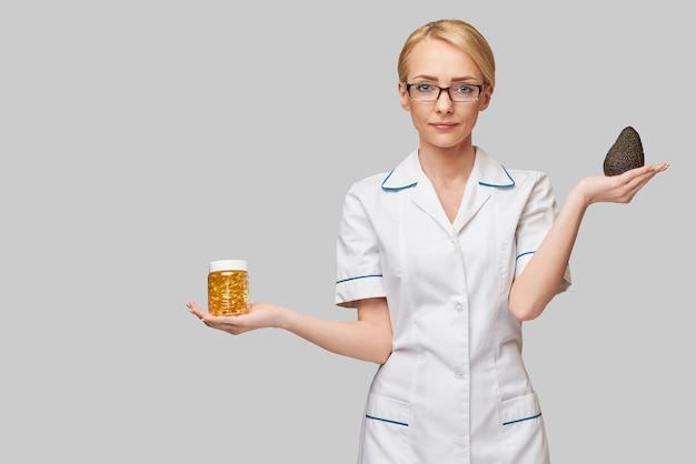 Concept de soins de santé et de régime - médecin nutritionniste ou cardiologue tenant de l'huile de poisson dans des capsules pour la vitamine d et les acides gras oméga-3 et l'avocat