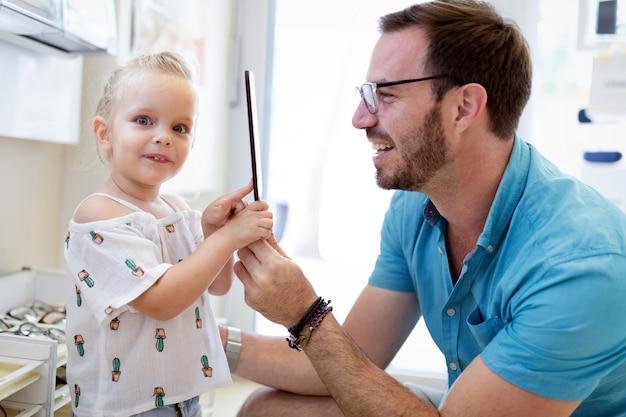 Concept de soins de santé, de vue et de vision. enfant heureux choisissant des lunettes avec son père au magasin d'optique