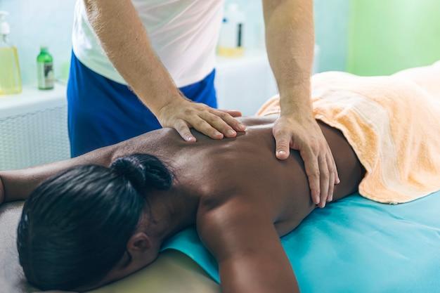 Concept de soins spa de massage. le physiothérapeute fait un massage du dos pour une femme noire. femme américaine se faire masser concept de soins spa de massage.