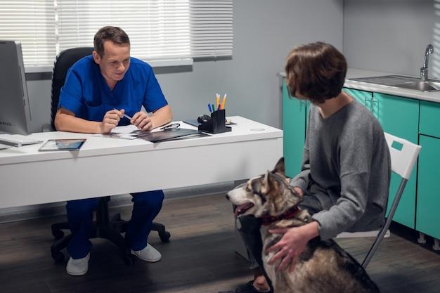 Concept de soins vétérinaires. un chien husky dans le bureau du vétérinaire avec son propriétaire.